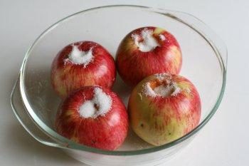 уложить яблоки в посуду для запекания, в отверстие насыпать сахар, сбрызнуть водой