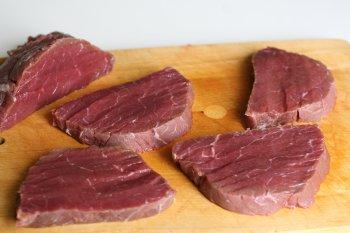 нарезать мясо поперек волокон толщиной 15—20 мм