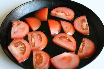 нарезать помидоры и положить на сковороду с маслом