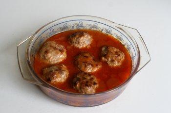 залить тефтели томатным соусом и отправить в духовку, тушить при закрытой крышке до готовности