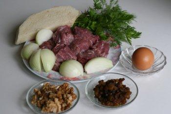 мясо нарезать на кусочки, приготовить лук, зелень, хлеб, яйцо, грецкие орехи и изюм